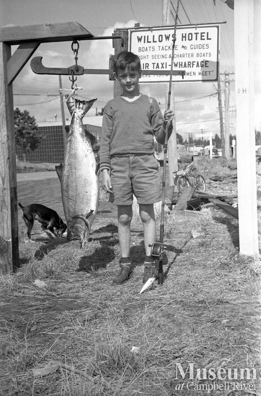Unidentified child with a salmon at the Willows Hotel