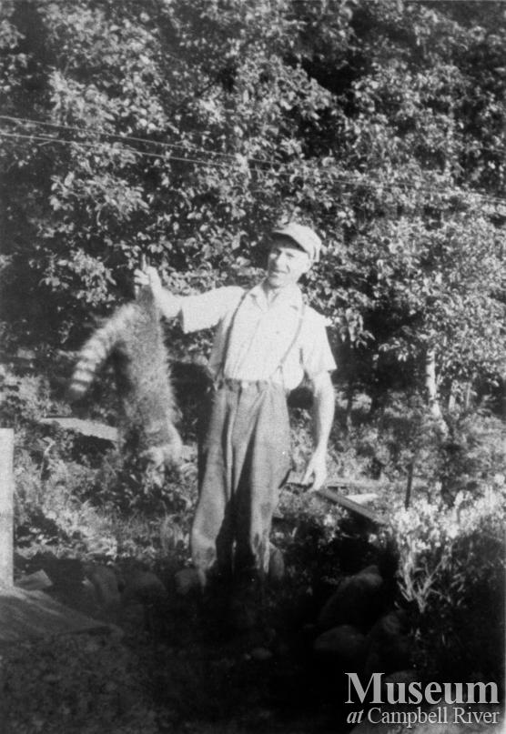 George Nunns with racoon that he trapped