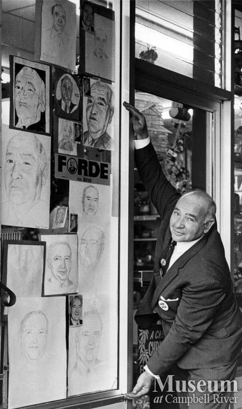 Ken Forde poses with many portraits of himself
