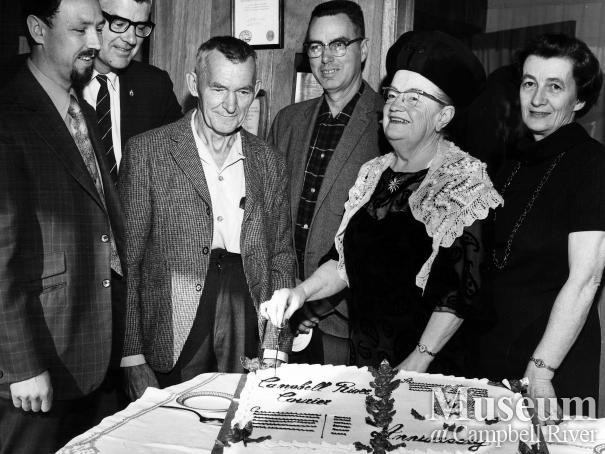 Lillie Thulin cuts cake to commemorate anniversary, 1971.